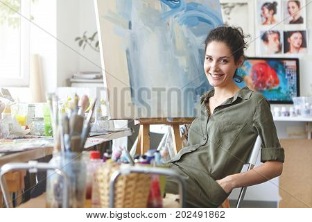 Professional Female Painter Sitting At Chair In Art Studio, Keeping Hands In Pockets Of Her Shirt, S