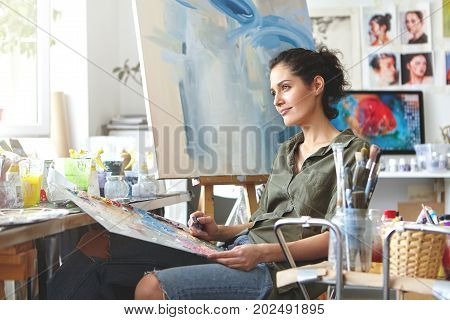 Thoughtful Dreamy Young European Female Artist Bringing Her Creativity To Life, Sitting In Her Moder