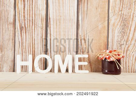 Word home with pot self made jam on wooden background