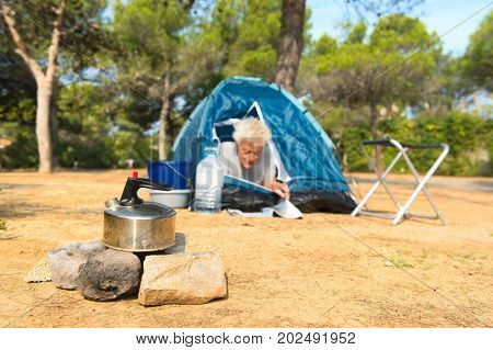 Man camping alone with blue dome tent for adventure reading a magazine