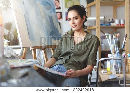 Trendy-looking Positive Talented Young Caucasian Woman Artist Relaxing On Chair Next To Easel In Wor