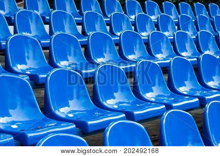 Rows of blue plastic stadium seats. Background