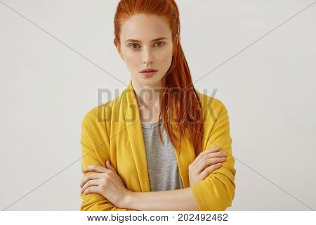Attractive Female With Reddish Pony Tail, Standing Crossed Hands Feeling Self-assuarance While Posin