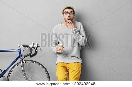 Young Male Traveller With Astonished Expression, Opening Mouth And Covering It With Hand, Keeping Pa