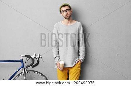 Studio Shot Of Attractive Man Drinking Coffee After Having Walk On Bicycle, Standing In His Room Aga