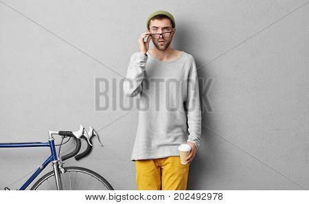 Clever sportsman looking through big glasses with serious expression drinking delicious hot coffee going to competitions or in gym. Serious male bicyclist standing indoors over grey background poster