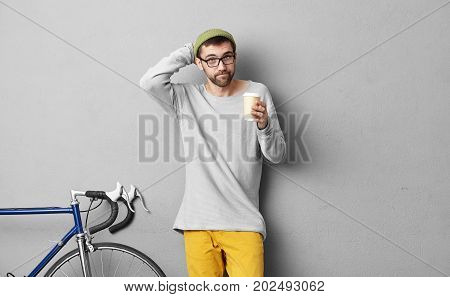Schoolboy Stratching His Head While Keeping Takeaway Coffee, Trying To Remember What He Should Take