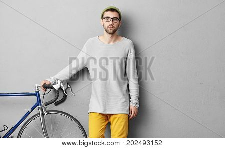 Serious Guy Dressed Casually, Selling Modern Bicycle, Keeping Hands On Handle Bar, Demonstrating Its