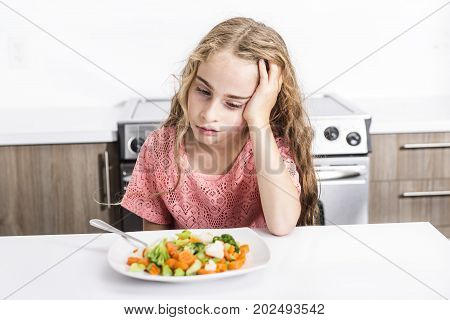 lovely girl showing boring expression with fresh colorful vegetables