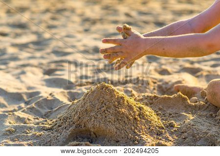 Baby Hands Playing With Sand On The Beach