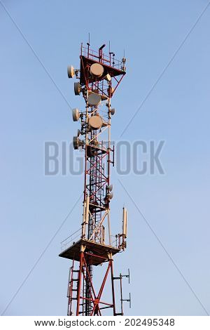 Telecommunications Tower And Satellite Dish Telecom Network On Blue Sky With Bright Sun Light