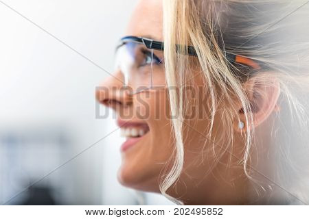 Closeup macro side view profile portrait of the young attractive happy smiling woman in protective eyeglasses