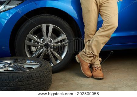 Man changed damaged car wheel. Casual guy changing wheel of car