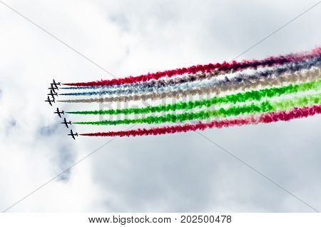 Group Of White Fighter Jet Airplane With A Trace Of Colorful Smoke Against A Blue Sky