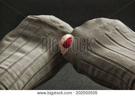 A toe with red nail polish is sticking out of a hole in a pair of gray socks.
