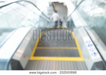 Looking along a descending escalator with objects around the escalator motion blurred. An unrecognisable silhouette of a person stands at the bottom of the escalator.