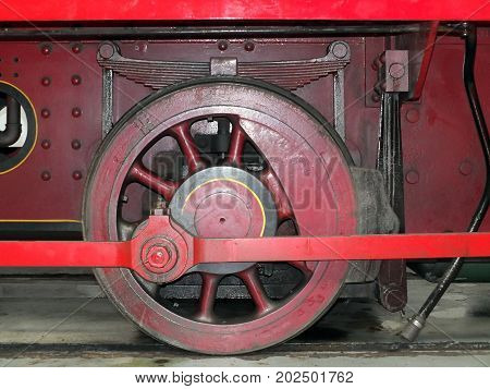 wheel of an old steam locomotive painted red with coupling rods and spring