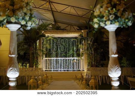 wedding venue aisle with candles in glass lanterns and arch, stylish wedding decor for evening wedding ceremony in garden, light close up. beautiful romantic place for love celebration