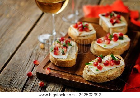 Pomegranate Brie balsamic crostini on a wood background