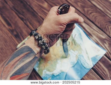 Unrecognizable man holding jackknife and pointing to map on a wooden background view of hand.