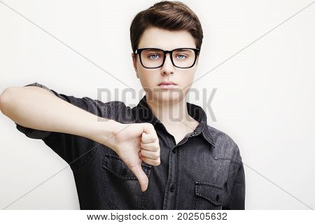 casual young man showing thumbs down to the camera on white background