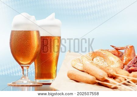 Oktoberfest beer pint glasses and german bavaria flag background national dishes pretzel maishund corn hot dog fried wings copy space