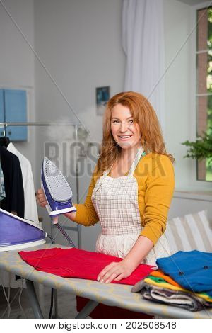 Foxy haired female at home ironing. Smiling mid aged housewife holding iron.