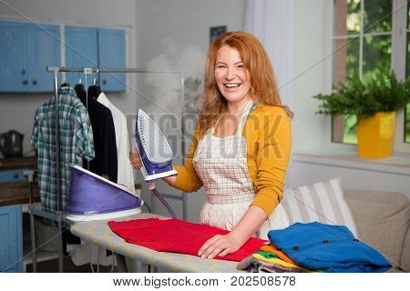 Ginger joyful female standing by ironing board. Mid aged beautiful woman ironing clothes at home.