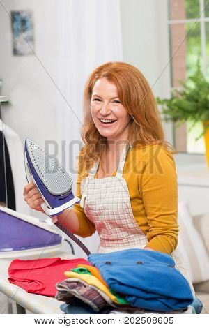 Portrait of mid aged foxy woman with iron. Female busy with housework routine ironing.