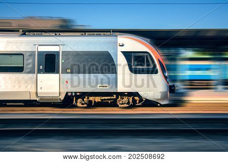High speed train in motion at the railway station at sunset in Europe. Modern intercity train on the railway platform with motion blur effect.  Moving passenger train on railroad. Transportation