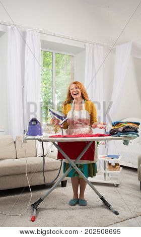 Foxy housewife standing by ironing board. Mid aged woman iat home busy with housekeeping work.