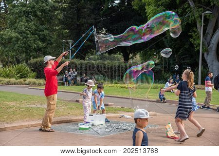 SYDNEY,NSW,AUSTRALIA-NOVEMBER 20,2016: Street busker and children playing with tri-string bubble wand and giant bubbles in Hyde Park in Sydney, Australia.