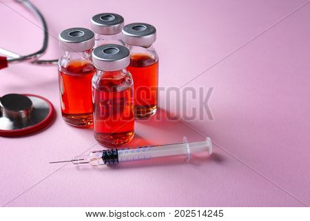 Ampules with vaccine, syringe and stethoscope on color background
