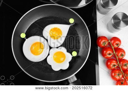 Cooking of delicious sunny side up eggs in molds, top view