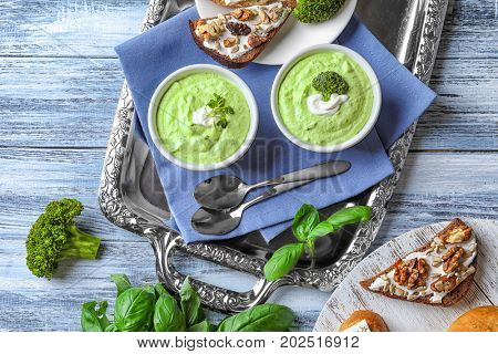 Composition with delicious creamy broccoli soup on metal tray