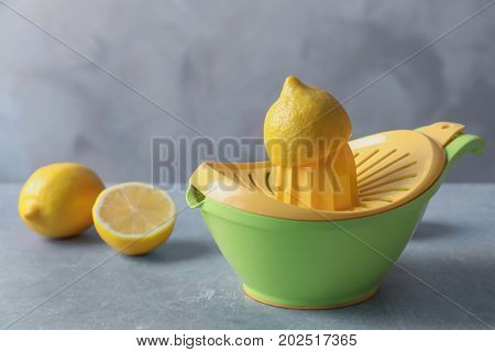 Plastic squeezer with fresh lemons on grey background