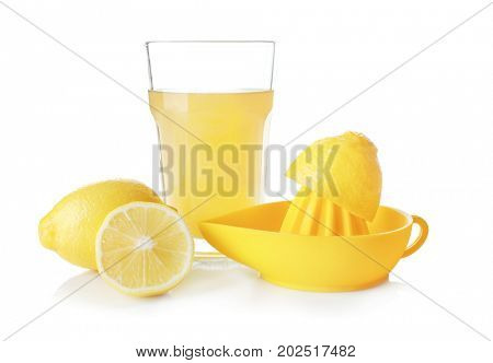 Composition with cut lemons, glass of juice and plastic squeezer isolated on white