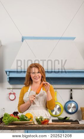 View of housewife in the kitchen dreaming holding carrot in hand. Lunch time, woman cooking diet meal.