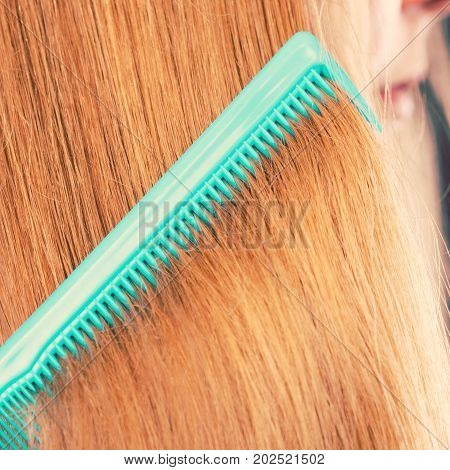 Combing and brushing concept. Routine everyday hygiene. Close up of detail green comb in red smoothy healthy female hair.