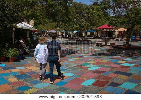 San Diego, California - August 31, 2017: a couple strolls, hand in hand, across the colorful plaza at the Spanish Village Art Center in  Balboa Park.