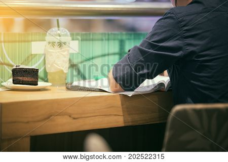 Asian Men Reading A Book And Drink Coffee And Cake For Relaxation At Coffee Cafe