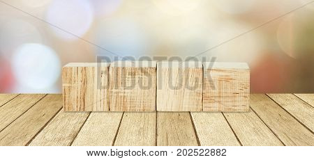 Four wooden cubes over perspective wood and blur abtract bokeh light background