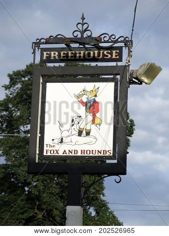 Reading England - August 4 2017: Closeup of The Fox and Hounds 19th Century Inn Sign againsh cloudy summers sky