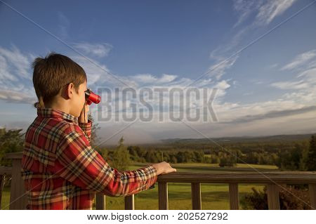 boy looking through binoculars outside. child standing by the wooden railing and holding binoculars. Copy space for your text