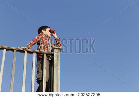 boy looking through binoculars outdoors. child standing by the wooden railing and holding binoculars on a background of blue sky. Copy space for your text
