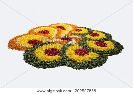 flower rangoli for Diwali or pongal or onam made using marigold or zendu flowers and red rose petals over white background with diwali diya in the middle, selective focus