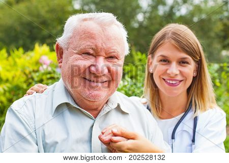 Happy grey haired senior man with friendly female doctor in the park