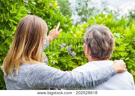Picture of a senior lady with her friendly caregiver in the park back view