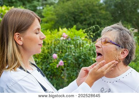 Female medical doctor examining elderly woman with sore throat in the garden