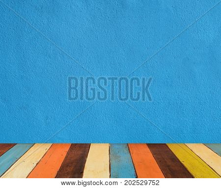 blue cement wall with colorful retro painted wooden floor
